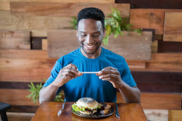 Heureux homme noir prend une photo de son repas de l'afficher sur ses médias sociaux - Photo
