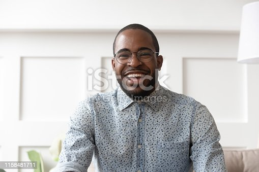 Happy cheerful young black man video calling looking at camera at home, smiling african guy communicate in internet chat recording vlog talking laughing skyping enjoy online conversation, webcam view