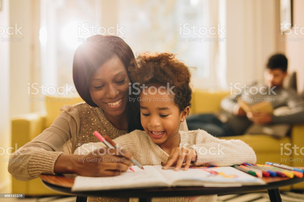 Happy black mother and daughter having fun while coloring in the living room. - Стоковые фото Африканского происхождения роялти-фри