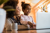Happy African American mother teaching her girl how to use computer at home.