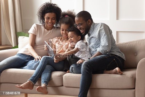 istock Happy black parents and children using digital tablet on sofa 1158481678