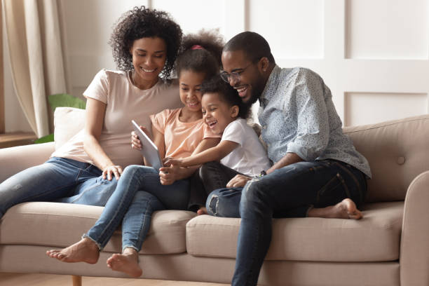 happy black parents and children using digital tablet on sofa - family foto e immagini stock