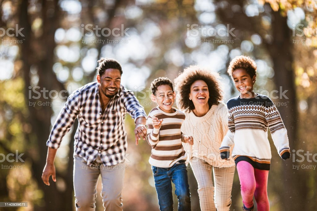 Playful African American family having fun while chasing in the park.