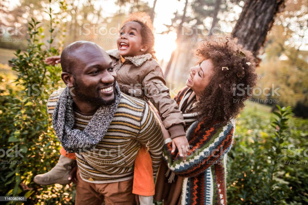 Happy African American family having fun in autumn day at the park....