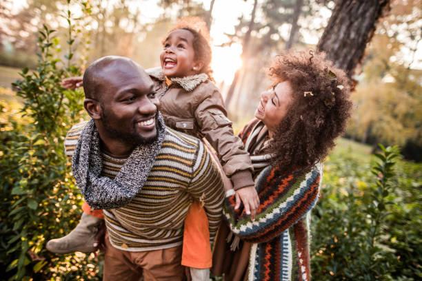 genitori neri felici che si divertono con la loro figlia al parco. - family foto e immagini stock