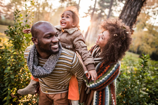 Happy black parents having fun with their daughter at the park. Happy African American family having fun in autumn day at the park. Father is piggybacking little girl. african american ethnicity stock pictures, royalty-free photos & images