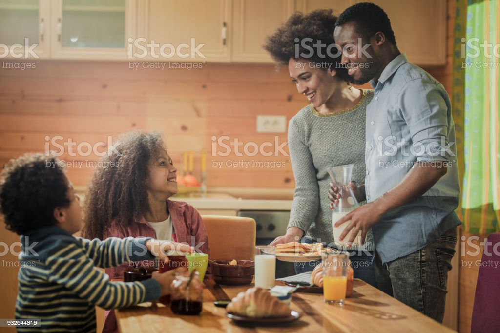 Happy African American parents serving breakfast to their kids in...