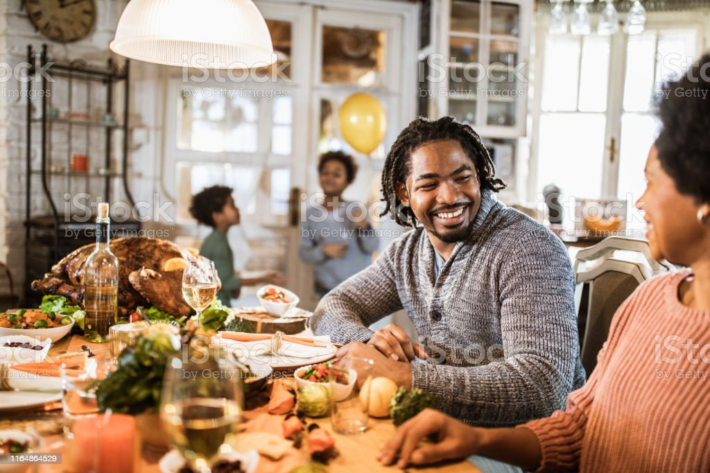Happy African American parents talking while having Thanksgiving meal...