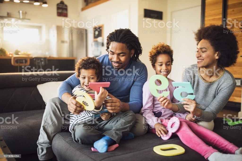 Young happy African American family learning numbers on sofa in the...