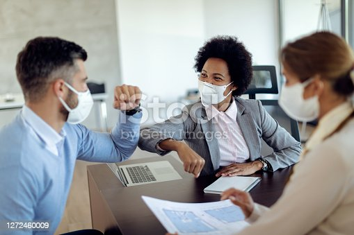 Happy African American real estate agent and her clients greeting with elbows in the office. They are wearing protective face masks due to COVID-19 epidemic.