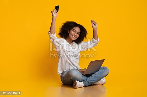 1173546354 istock photo Happy Black Woman Celebrating Success With Laptop And Credit Card 1212728411