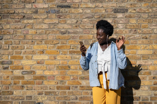glücklich schwarze frau musikhören mit kopfhörer auf der straße - geräusche app stock-fotos und bilder