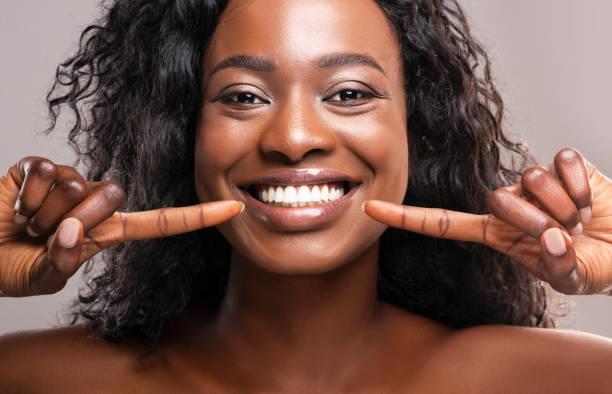 gelukkige zwarte vrouw die naar haar perfecte witte tanden wijst - menselijke mond stockfoto's en -beelden