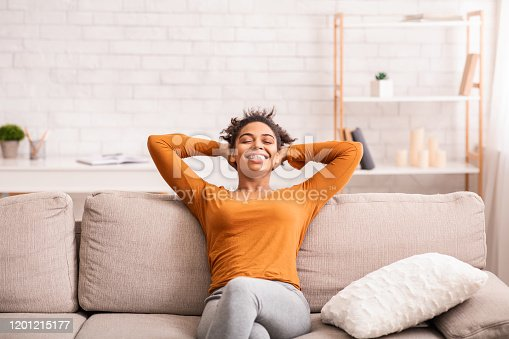 Weekend At Home. Happy Black Woman Relaxing Sitting On Sofa Holding Hands Behind Head Enjoying Lazy Day-Off Indoor