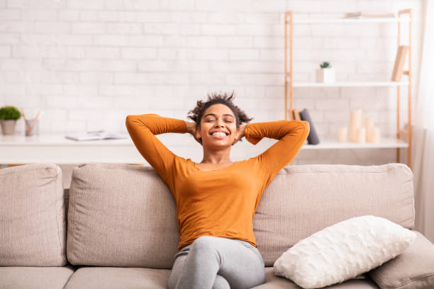 Happy Black Woman Relaxing Sitting On Sofa At Home stock photo