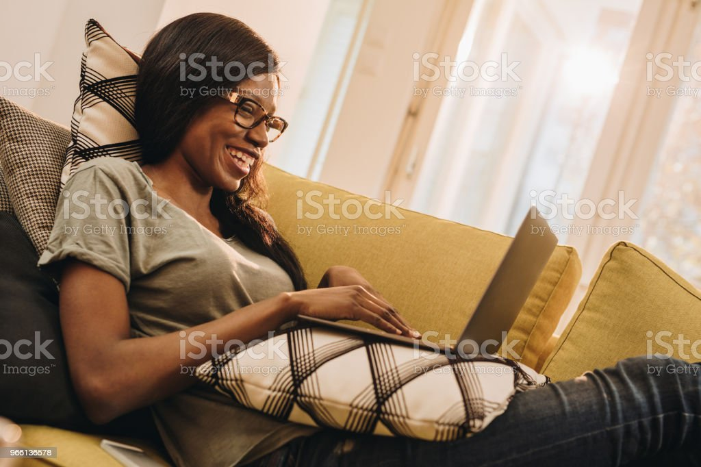 Happy black woman surfing the net on laptop at home. - Royalty-free Adult Stock Photo