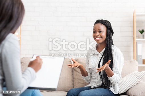 Successful therapy. Happy black female patient talking to psychologist at her office, expressing gratitude