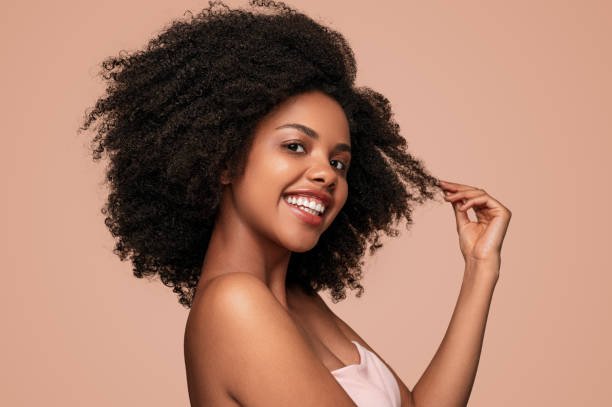 Happy black woman touching clean hair stock photo
