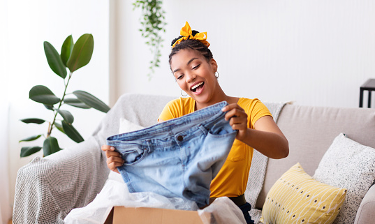 Happy black woman unpacking clothes after online shopping