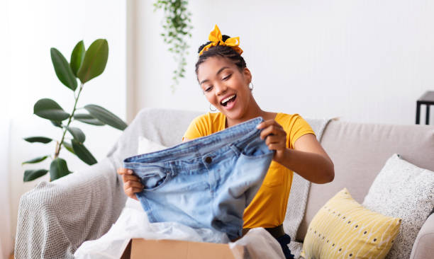 Happy black woman unpacking clothes after online shopping Delivery Concept. Happy black woman sitting on couch and holding jeans, unboxing cardboard package, free space clothes in box stock pictures, royalty-free photos & images