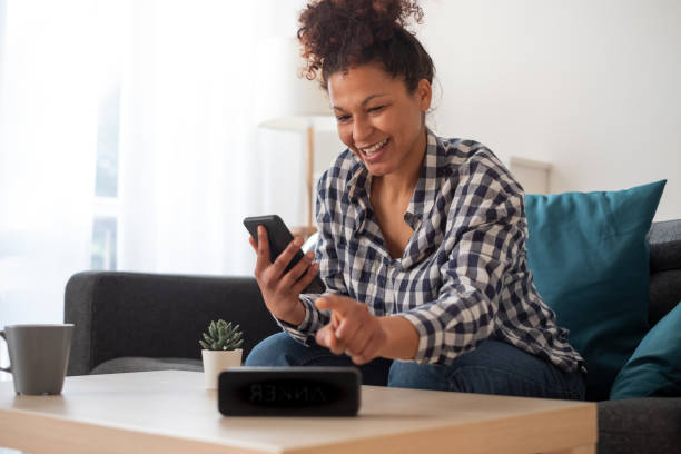 Happy black woman using smart speaker at home stock photo