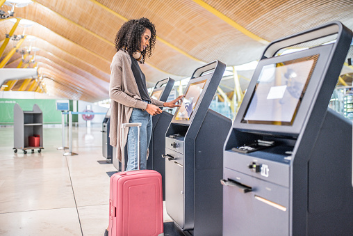 happy black woman using the check-in machine at the airport getting the boarding pass.