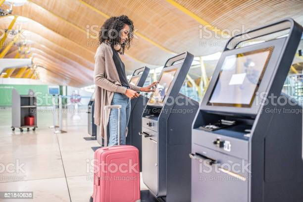 Happy black woman using the checkin machine at the airport getting picture id821840638?b=1&k=6&m=821840638&s=612x612&h=9mniwf68si5wgqdf4urw1o l8xybl3e9efxzx8ruobs=