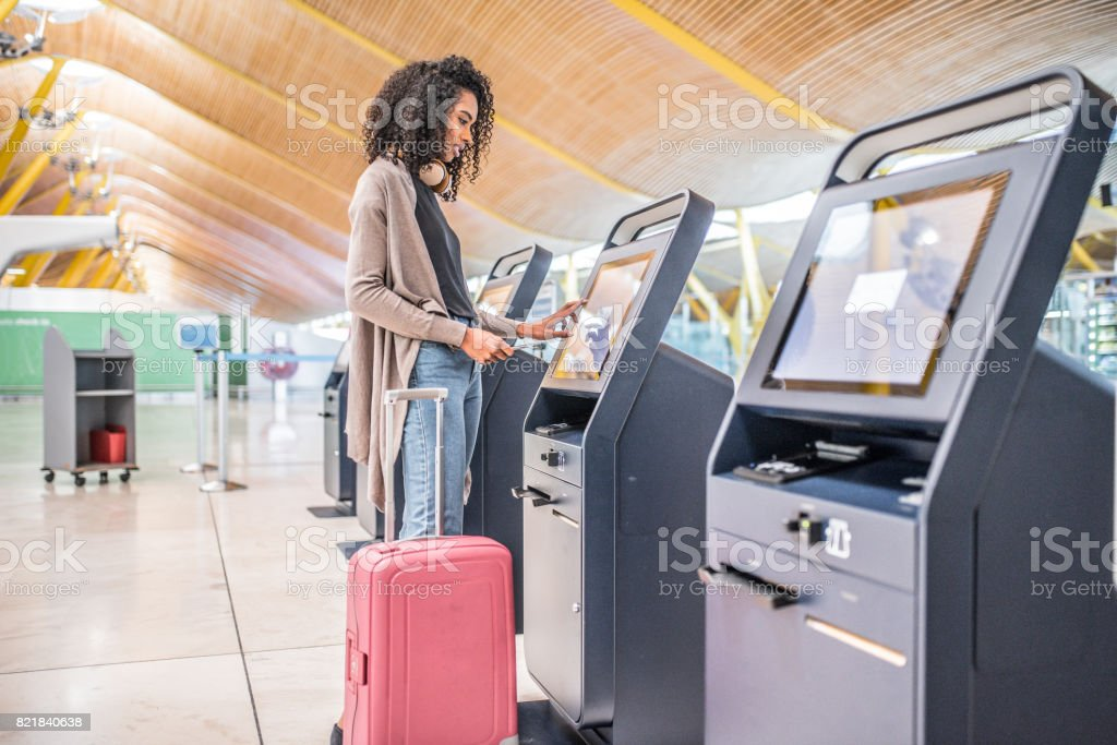 happy black woman using the check-in machine at the airport getting the boarding pass. stock photo