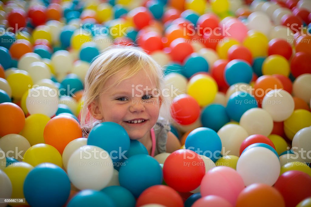 Happy blond girl plays in a ball pool stock photo