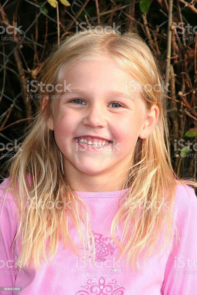 happy blond girl sitting on a bench stock photo