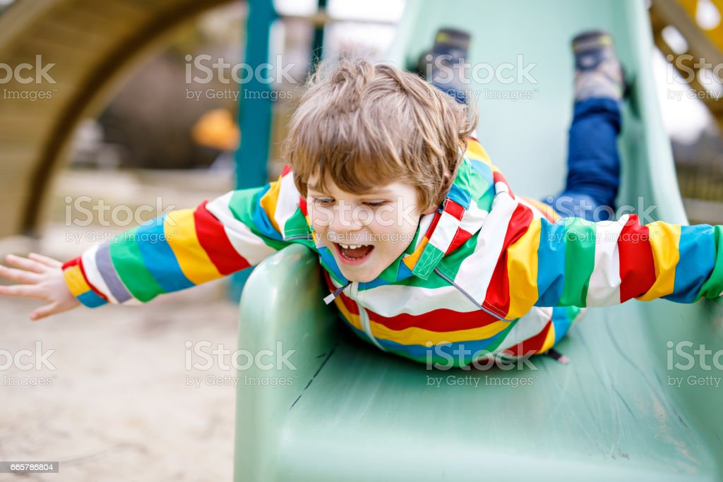Happy blond kid boy having fun and sliding on outdoor playground stock photo