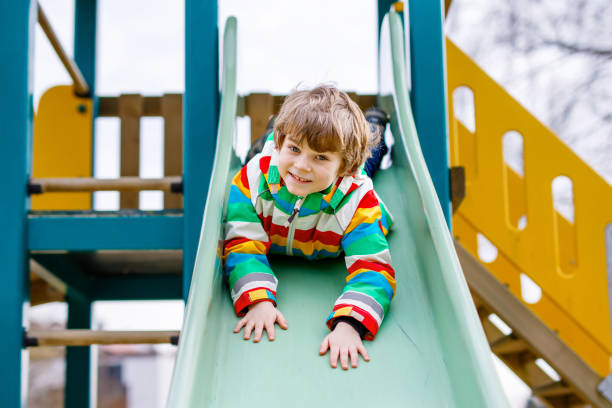 Happy blond kid boy having fun and sliding on outdoor playground stock photo