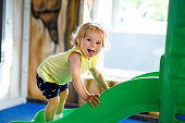 Happy blond little toddler girl having fun and sliding on indoor playground at daycare or nursery. Positive funny baby child smiling. Healthy girl climbing on slide