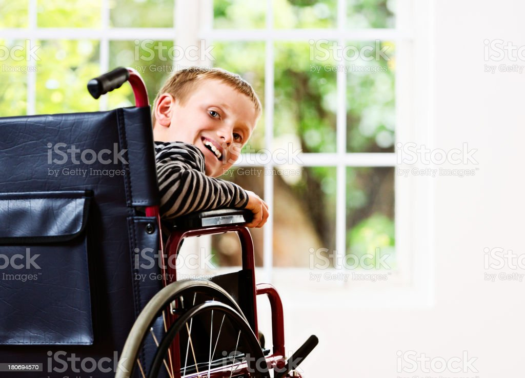 Happy blond schoolboy in wheelchair seems to be recovering stock photo