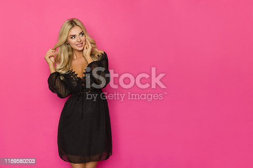 Happy beautiful blond woman in black lace mini dress is  looking to the side at copy space. Three quarter length studio shot on pink background.