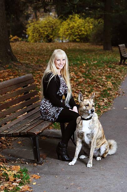 glücklich blonden frau mit hund sitzen auf der bank im herbst - hunde strumpfhosen stock-fotos und bilder