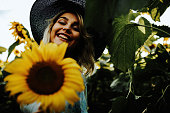 Happy blonde female in the sunflower fields, summer day, full bloom sunflower