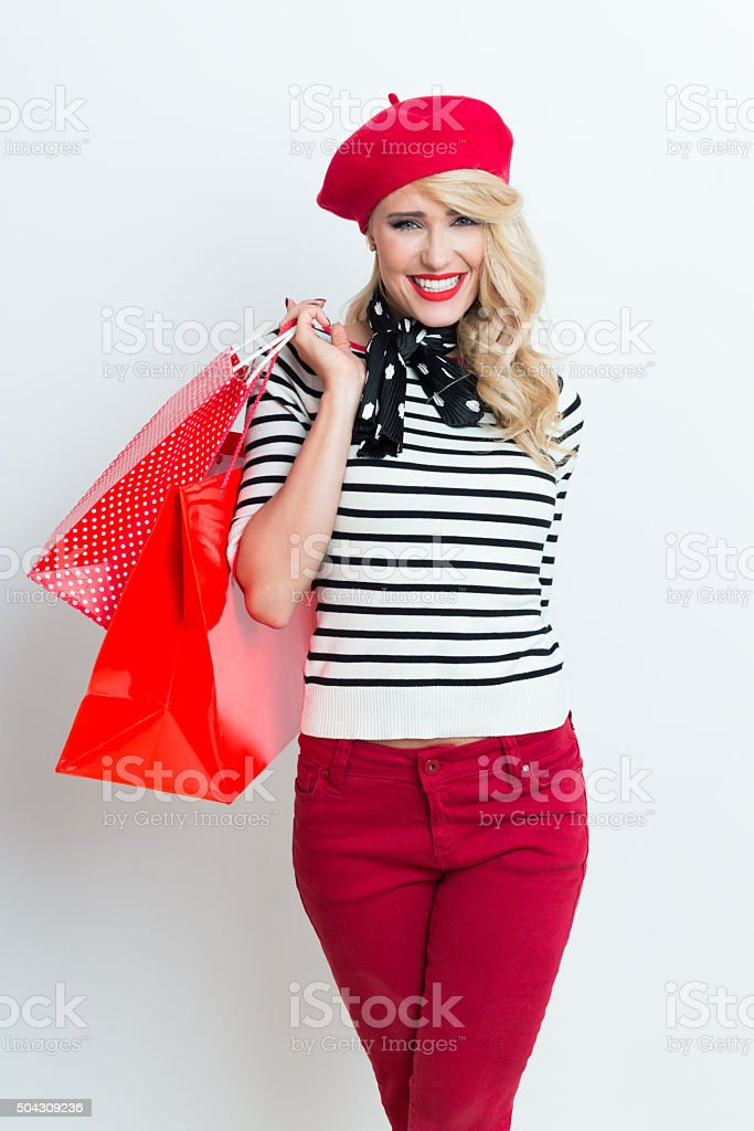 Happy blonde french woman wearing red beret, holding shopping bags Portrait of happy beautiful blonde woman in french outfit, wearing a red beret, striped blouse and neckerchief, holding shopping bags, laughing at camera. Adult Stock Photo