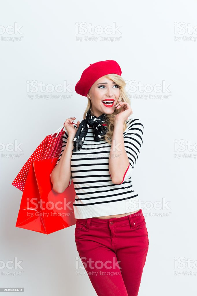 Happy blonde french woman wearing red beret, holding shopping bags Portrait of happy beautiful blonde woman in french outfit, wearing a red beret, striped blouse and neckerchief, holding shopping bags. Adult Stock Photo