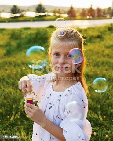 507271044istockphoto Happy blonde girl blowing soap bubbles 469703582