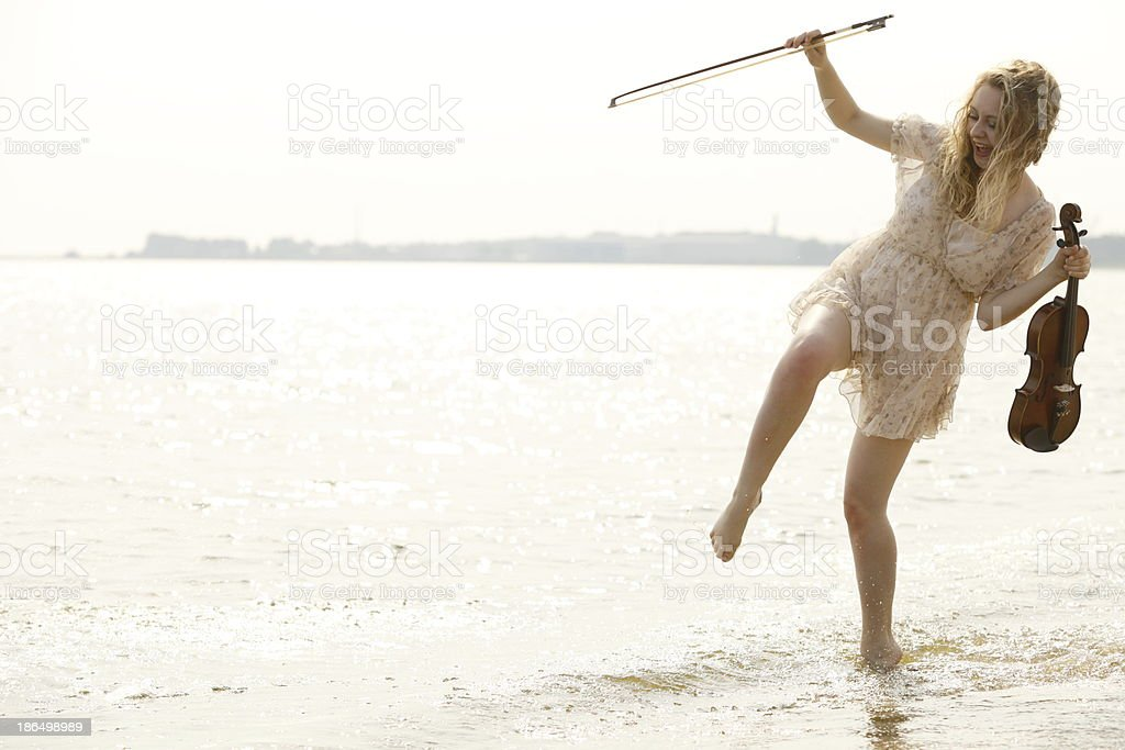 Happy blonde girl with a violin outdoor royalty-free stock photo