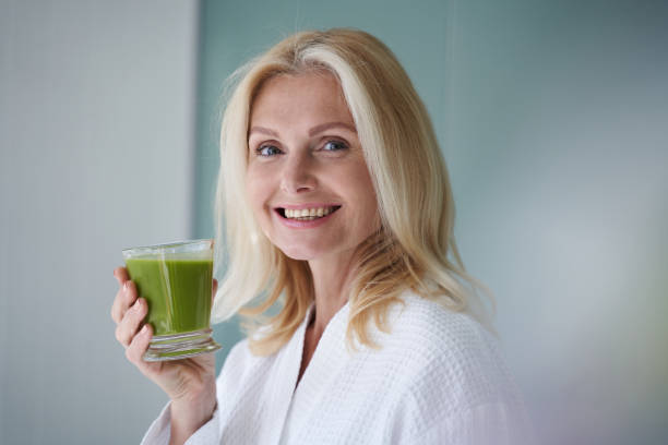 Happy blonde lady standing with healthy drink stock photo
