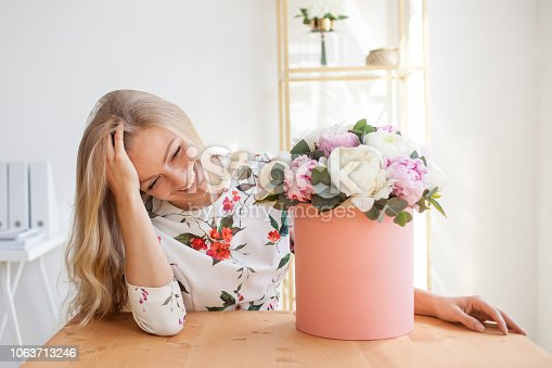 Happy blonde woman in a modern office with flowers in a hat box. Bouquet of peonies. Flower delivery to the workplace