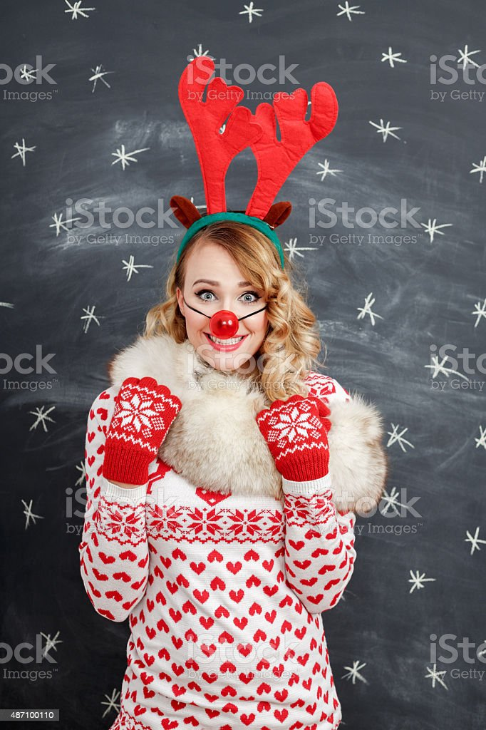 Happy blonde woman in winter outfit and reindeer antlers headband stock photo