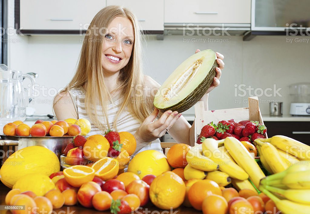 Happy blonde  woman  near heap of fruits at home kitchen royalty-free stock photo