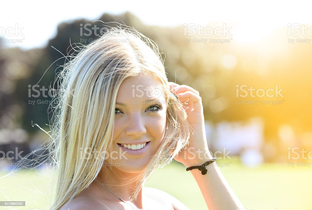 Happy blonde young adult woman enjoying sun stock photo