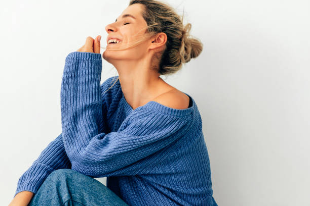 Happy blonde young woman dressed in cozy knitted blue sweater, laughing during conversation and relaxing. Beautiful blonde female smiling and resting at home. stock photo