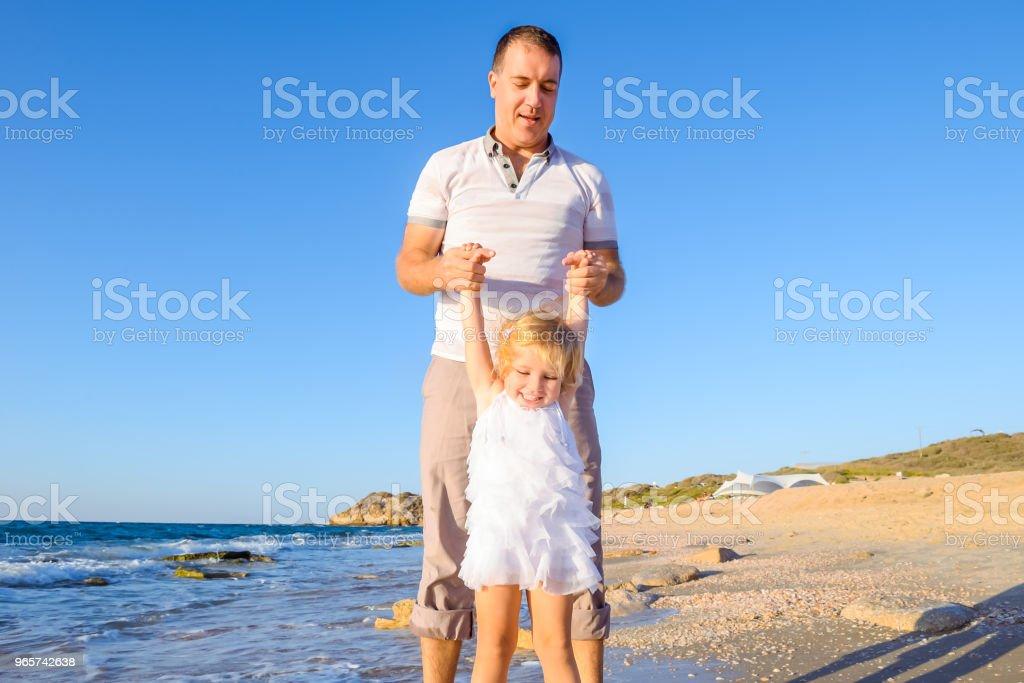 Gelukkig blondy kind meisje met haar vader hand in hand en plezier wandelen op het strand. Familie vakantie, reizen-concept. Fel zonlicht. Kopieer ruimte. - Royalty-free Alleenstaande vader Stockfoto