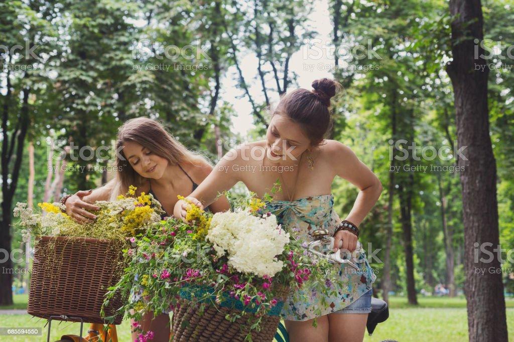 快樂的波西米亞風別致女孩收集野生花卉在自行車上騎 免版稅 stock photo