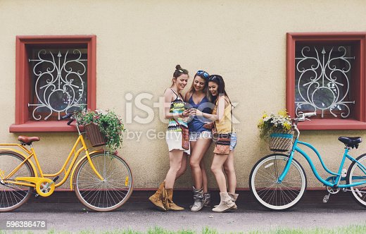 Happy boho chic stylish girls look at mobile phone near house facade. Beautiful women and bicycles with baskets full of wild flowers. Female friends, youth fashion, summer leisure in park concept.